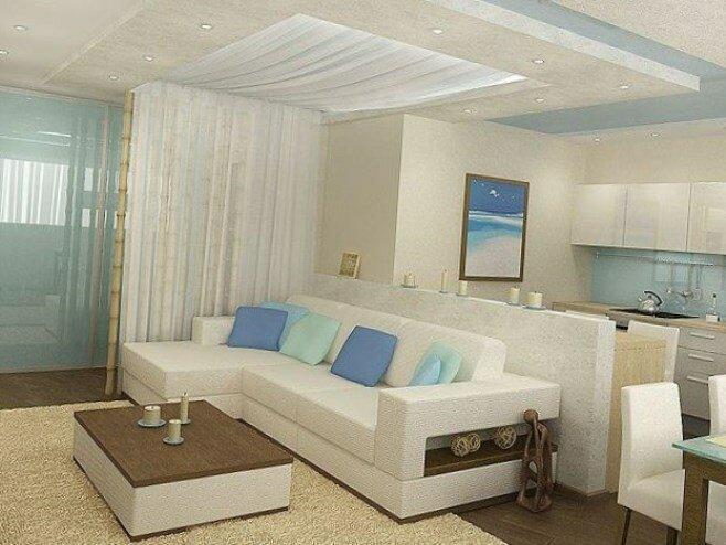 Большой диван в гостиной, объединенной с кухней