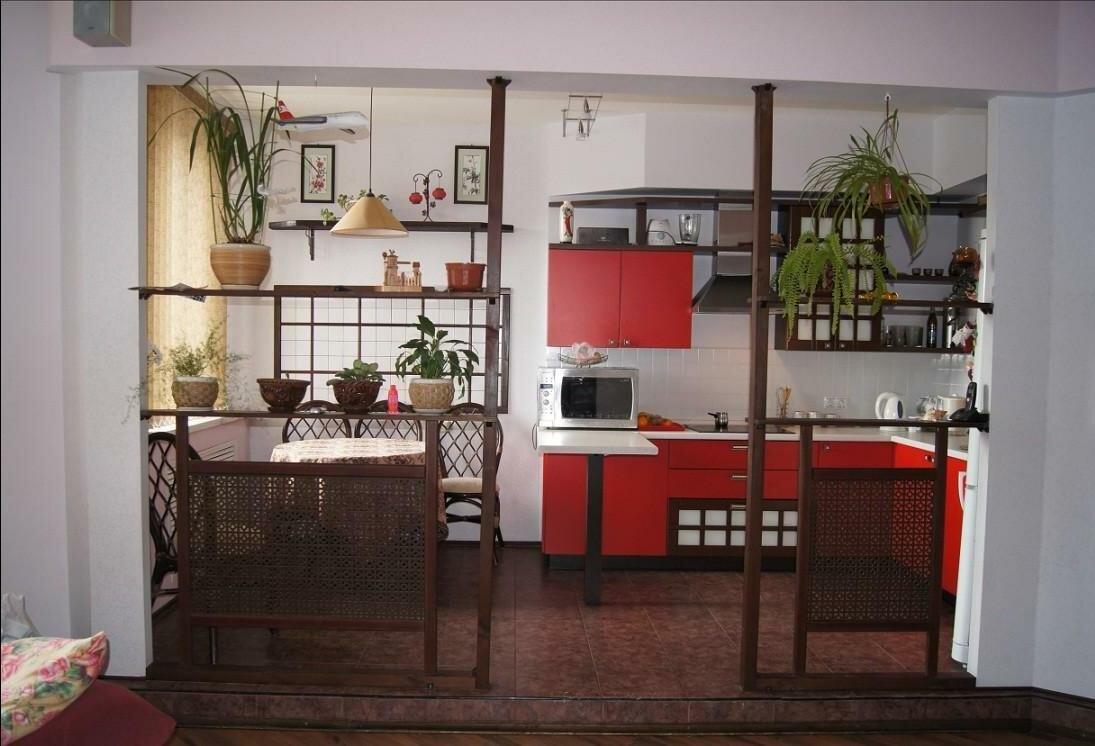 Кухня с красным фасадом, совмещенная с гостиной